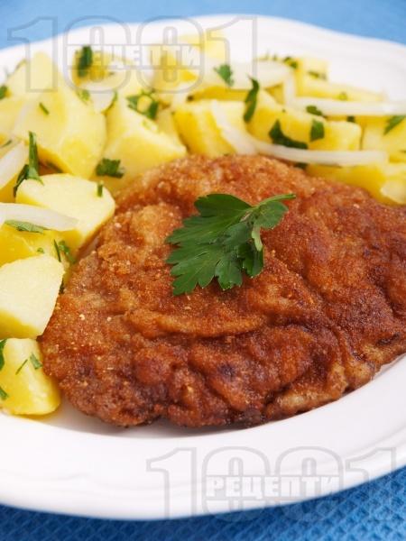 Класически виенски шницел от телешки шол паниран в брашно, галета и яйца с картофена гарнитура - снимка на рецептата